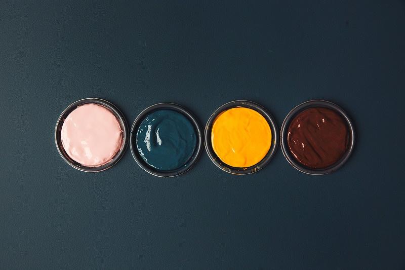 蓝色桌子上充满活力的颜料罐照片(Vibrant Pots O_爱给网_aigei_com